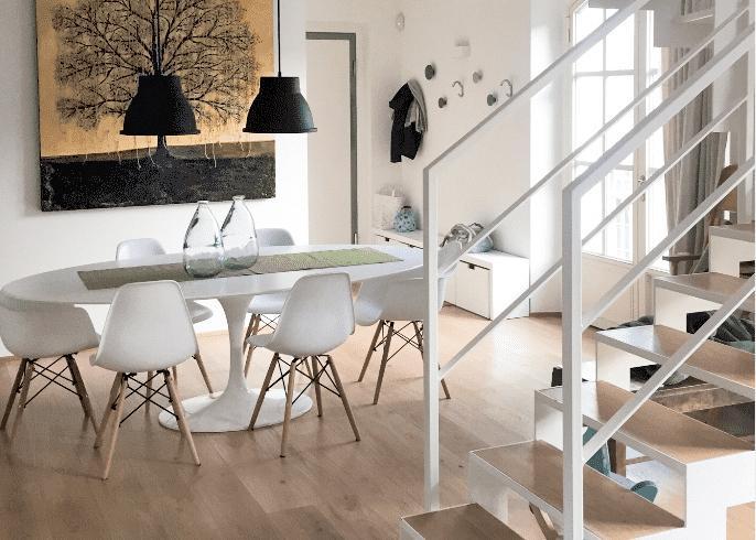 zona pranzo in soggiorno tavolo e sedie bianchi, scala bianca pavimento gradini in parquet