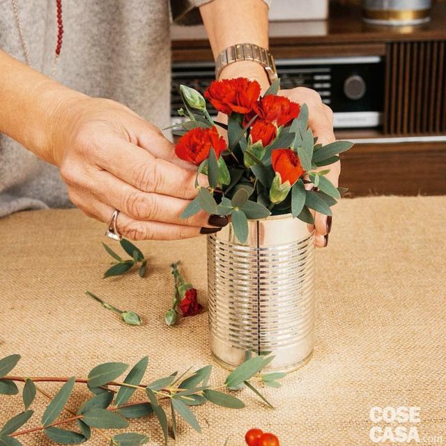 4. Prendere qualche stelo di Dianthus e tagliare a 45 gradi tutti i fusticini che portano fiori. Accompagnarli delicatamente nella fase di introduzione nella spugna per evitare che si spezzino. Intervallare i fiori alle foglie, facendo in modo che i fiori risultino ben distribuiti nella composizione.