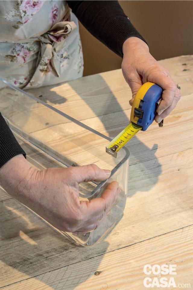 1 Versare l'acqua in un vaso rettangolare per circa un terzo della sua altezza, dopodiché realizzare una griglia con lo scotch trasparente di circa 4x4 cm. Con un centimetro, misurare la larghezza utile del vaso (il nostro è di 15 cm) e anche quella dello scotch (circa 1,5 cm). Sottrarre dal calcolo per due volte lo scotch (15 - 3 = 12 cm). Dividere lo spazio residuo in tre (12 : 3 = 4) e fissare due nastri di scotch ogni 4 cm che collegano un lato corto all'opposto.