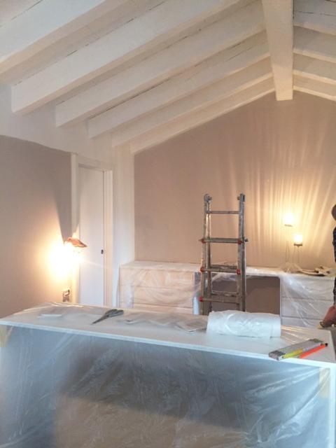 Camera sottotetto travi bianche lavori e mobili coperti