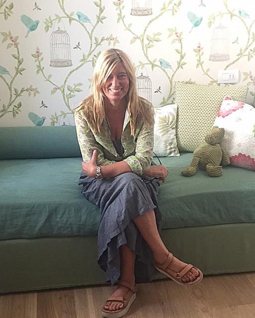 Clara Bona nella cameretta con tappezzeria disegno botanico e gabbiette uccellini