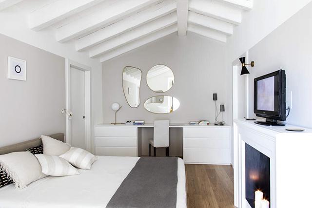 camera sottotetto soffitto legno bianco pareti grgie finto camino