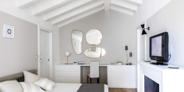 camera sottotetto soffitto legno bianco pareti grigie finto camino