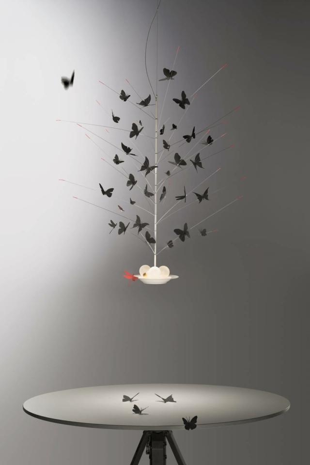 La sospensione La Festa delle Farfalle di Ingo Maurer, design Ingo Maurer & Team, è formata da trentaquattro farfalle e una libellula, in cartoncino tagliato a laser, che si posano tra i rami di un sottile fusto sospeso su un piatto di porcellana su cui sono presenti tre lampadine appoggiate, non alimentate, ma illuminate per trasparenza dai Led integrati nel piatto. I Led emettono luce verso l'alto e verso il basso creando un effetto soffuso che aumenta la poesia della composizione. Misura ø  60 x H 110 cm. www.ingo-maurer.com