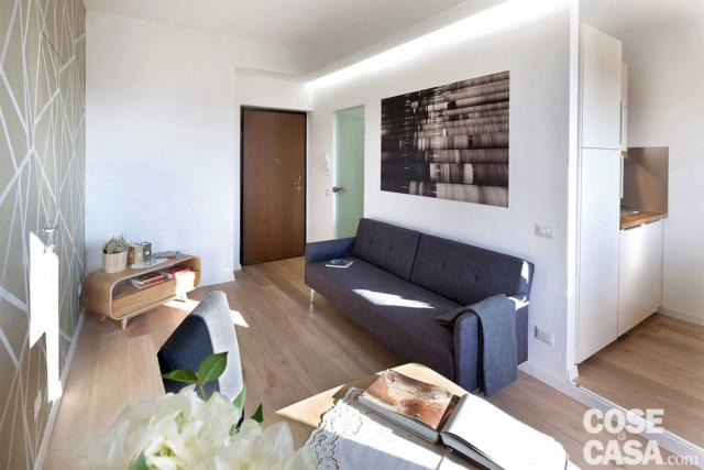 ingresso-sul-soggiorno con divano grigio e strisce a led
