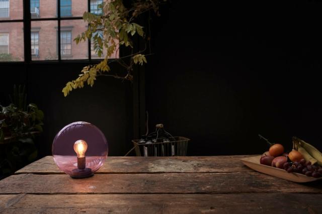 La lampada da tavolo Bubble Glass di Ledvance ha la forma di una sfera in vetro colorato in cui è visibile la lampada a led a filamento. Il corpo è in acciaio nero satinato.  Misura ø  24,5 cm. www.ledvance.it
