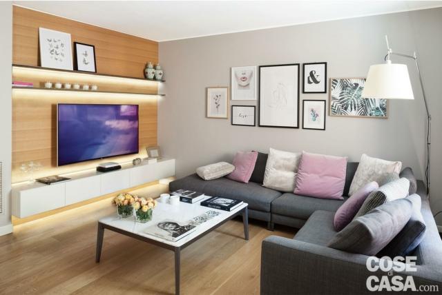 soggiorno con divano ad angolo grigio tavolino e tv con strisce a led a parete
