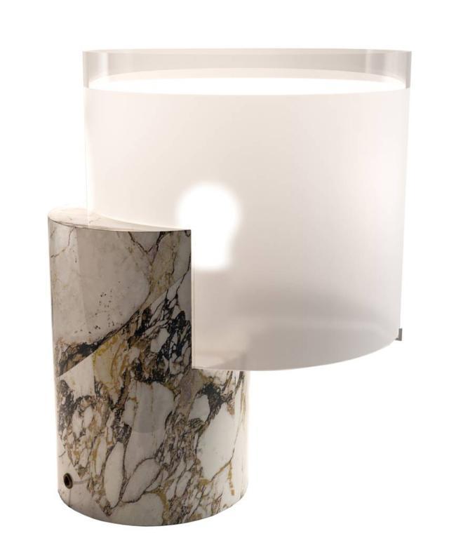 La lampada da tavolo Lea di Tato, design Matteo Nunziati, ha un design semplice impreziosito dai materiali con cui è realizzata: pregiato marmo lavorato in Toscana e vetro soffiato sabbiato veneziano. È composta da due semplici cilindri che si intersecano  tra loro. Misura L 30 x P 35 x H 40 cm.  www.tatoitalia.com