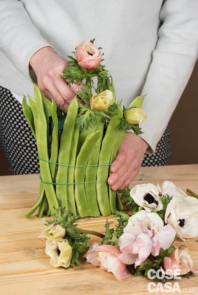 Con il coltellino tagliare l'altezza degli steli degli anemoni a circa 6-7 cm. Poi introdurre nella spugna i fiori, iniziando dagli angoli e lasciandoli sporgere leggermente. Accompagnarli per evitare che gli steli si spezzino.