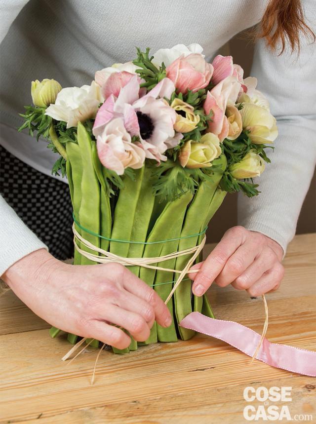 """Completare la composizione alternando fiori aperti a fiori chiusi e distribuendo le sfumature e le altezze in modo che la composizione risulti uniforme da tutti i lati. Infine, legare i fagiolini con un paio di giri di rafia e chiudere con un nodo ben fermo. Eliminare gli elastici. Terminare il lavoro avvolgendo il nastro sopra la rafia, fare un fiocco e dargli """"forma"""" con le mani."""