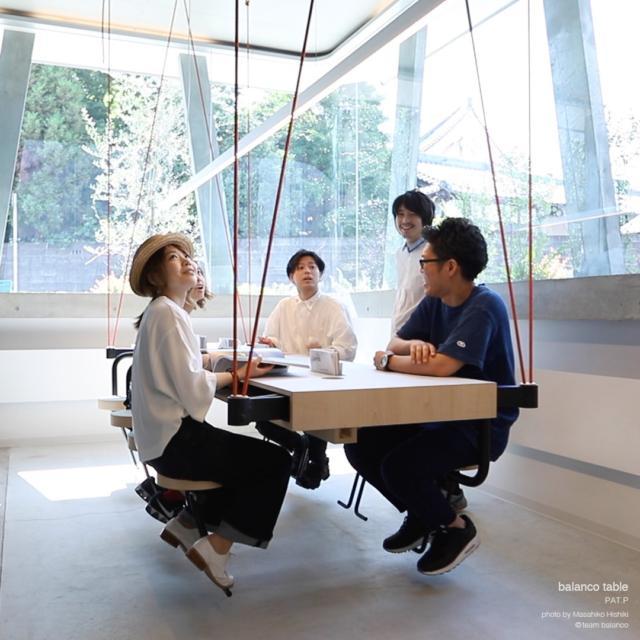 """Il """"Balanco table"""" del Team Balanco in mostra in Fonderia Napoleonica Eugenia, da 2 o da 8 posti, prende il nome da un termine portoghese con il significato di """"oscillante"""". È un tavolo sospeso che vuole creare un senso di comunità nello spazio architettonico. Ondeggiare è un'emozione che cattura chi la prova, un movimento che fa sentire ogni persona seduta parte di un gruppo. Ma rimanda anche alle oscillazioni concettuali dell'equazione che ha ispirato il progetto: """"Architettura come arredo per la vita quotidiana – arredo come giardino che trasforma il paesaggio – giardino come architettura che crea uno spazio privato."""""""