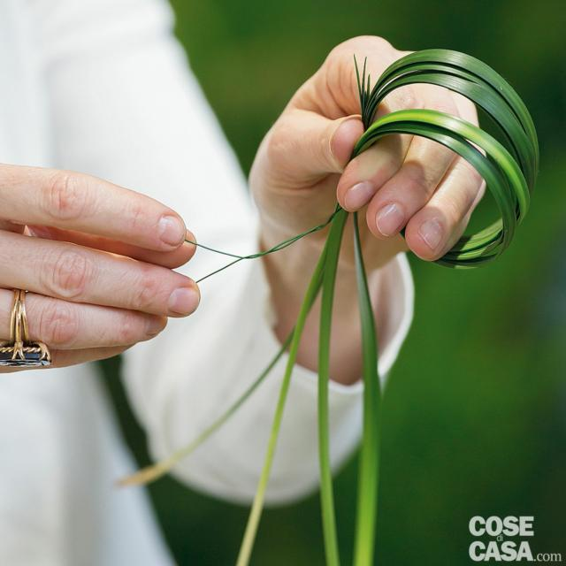 """4. Prendere 4 foglie di steelgrass e, tenendo ben salde le estremità tra pollice e indice, avvolgerle intorno alla mano due volte. Separare i fili e formare due cerchi distinti, uniti in basso tra le dita. Poi con un filo di ferro lungo almeno 15 cm, legare gli steli alla base. La parte restante di filo deve essere arrotolata su se stessa: servirà come """"gambo"""" per infilare lo steelgrass nella spugna. Tagliare le foglie in eccesso sotto la chiusura del filo di ferro. Ripetere con le altre 4 foglie."""