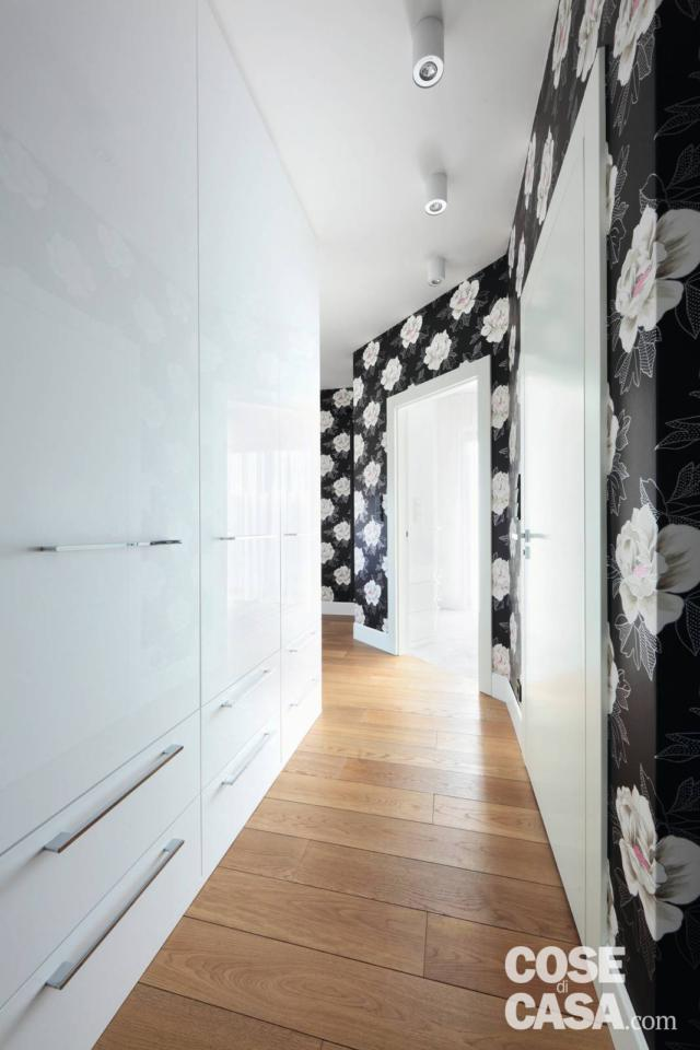 A crocked hallway with shiny, built-in cupboards and black and white floral wallpaper