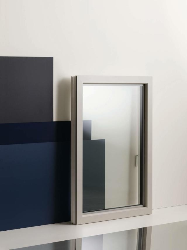 Il rivestimento esterno di alluminio, abbinato al PVC interno (isolante, riciclabile e di semplice manutenzione) della finestra a un'anta FIN-90 Nova-line Plus di Finstral, oltre a un'ampia personalizzazione cromatica garantisce resistenza nel tempo e stabilità. In questa versione l'esterno è di alluminio grigio ghiaia struttura fine, con smaltatura grigio seta lucido, mentre l'interno è di PVC bianco satinato.