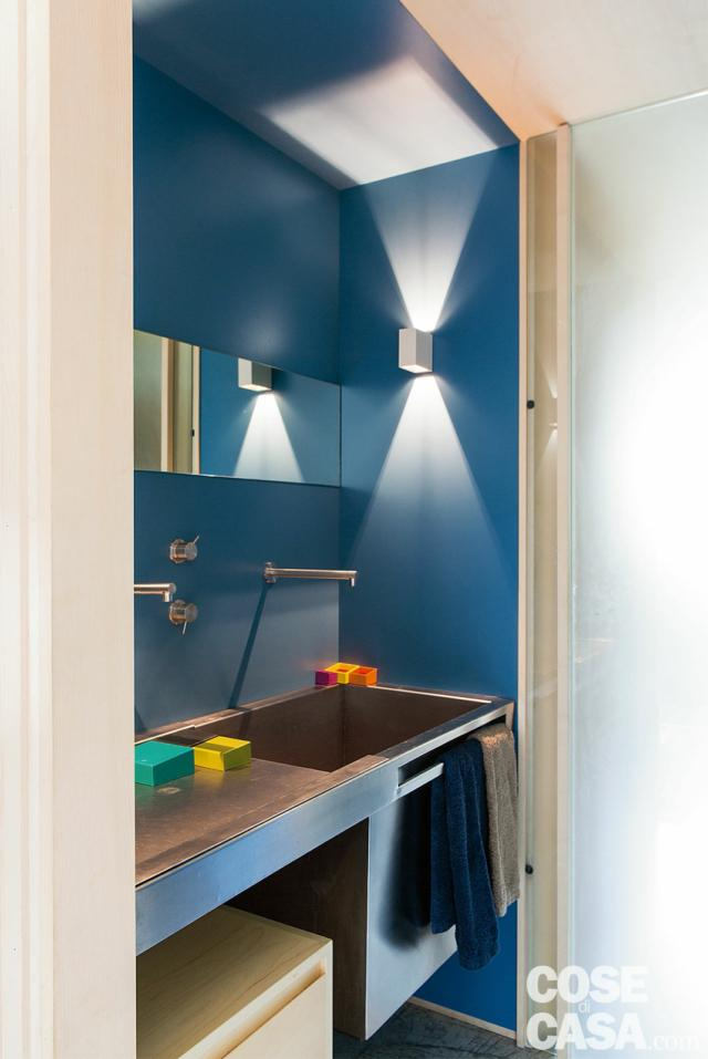 bagno, lavabo sospeso in acciaio, applique, rivestimenti a parete in laminato blu, porta scorrevole casa 110 mq