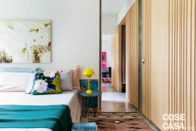 camera matrimoniale, dettaglio, letto, portariviste basso in pallet, parete rivestita in legno di acero, specchio
