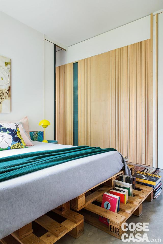 casa 110 mq   con camera matrimoniale, letto, cuscino a fiori comodino, lampada da tavolo vintage gialla, tappeto, parete rivestita in legno di acero, specchio