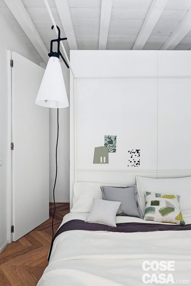 Camera matrimoniale, letto, lampada, ingresso della cabina armadio dietro al letto