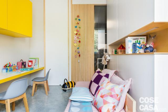 camera ragazzi, porta scorrevole in legno, postazione studio doppia, pensili gialli, armadio con nicchia orizzontale centrale, divano-letto, cuscini fantasia, pavimento in cemento casa 110 mq