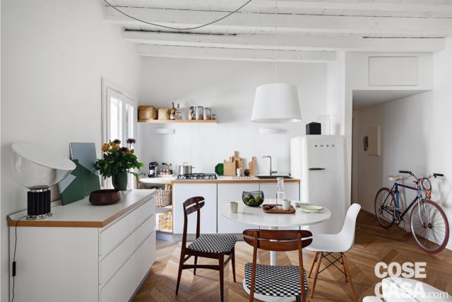mini bilocale, zona cottura, tavolo da pranzo rotondo, sedie, credenza, lampada a sospensione bianca, pavimento in parquet
