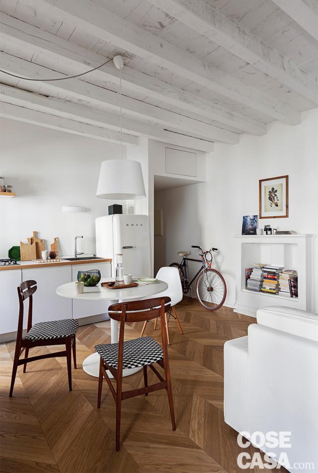 travi a vista, area living, tavolo da pranzo, sedie in legno con seduta imbottita, zona cottura, frigorifero anni '50