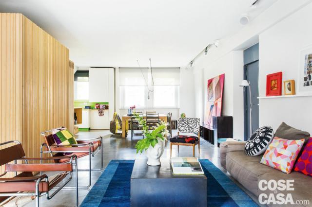 casa di 110 mq con open space, zona conversazione, divano, sedie bauhaus, tappeto azzurro, lampada da terra, pavimenti in cemento colore naturale