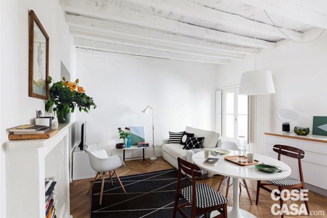 mini bilocale, soggiorno, zona pranzo, divano bianco, finto camino, travi a vista tinteggiate in bianco