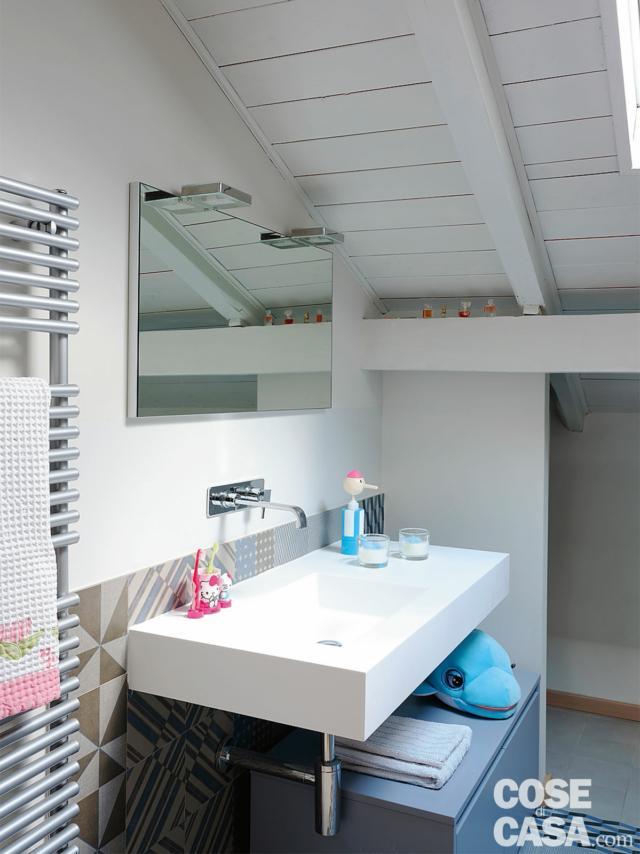 bagno nel sottotetto, falda inclinata, travi a vista, lavabo sospeso, cassettiera, specchio, scaldasalviette