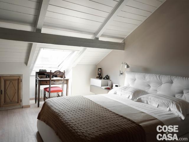 recupero del sottotetto, camera matrimoniale, letto con testiera capitonné rivestita in tessuto bianco, lucernario, pavimento in parquet, applique per la zona lettura