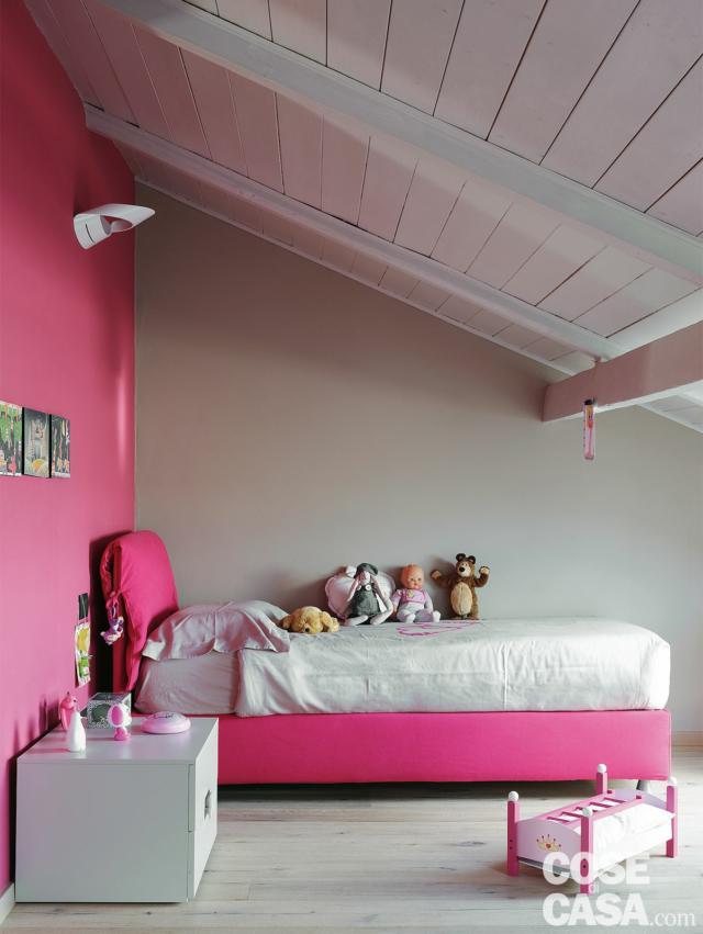 recupero del sottotetto, camera ragazzi, letto singolo tessile, comodino, parete e tessuti in finitura fucsia, tetto inclinato, travi e assito in legno