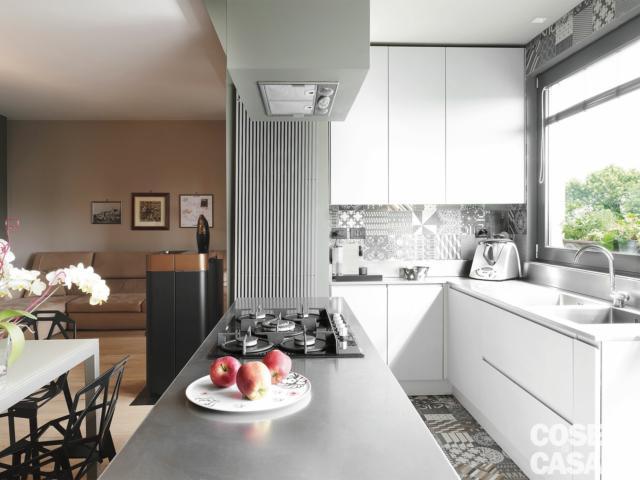 cucina, bancone a isola con piano cottura, cappa incassara, radiatore, composizione in laccato bianco, lavello integrato nel piano, vetrata