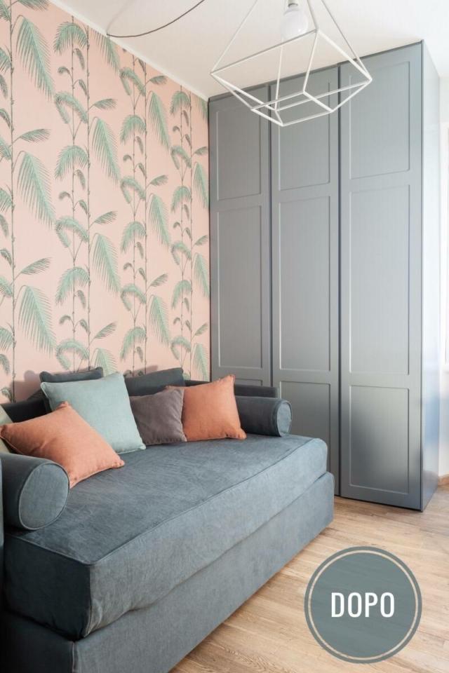 camera degli ospiti con divano letto grigio, cuscini colorati, carta da parati rosa con foglie verdi
