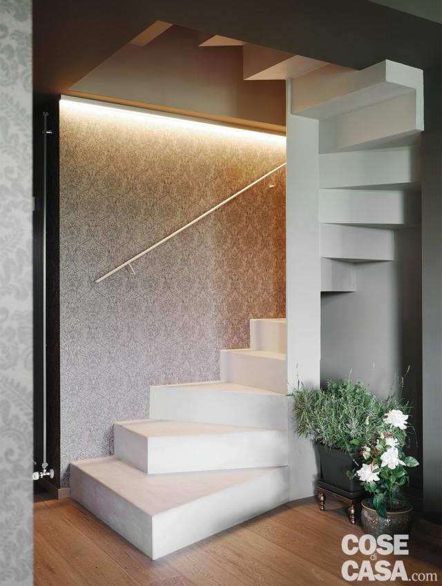 scala elicoidale, corrimano in acciaio, pareti rivestite con tappezzeria, pavimento in parquet