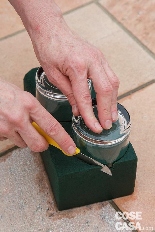 2. Lasciare affondare la mattonella di spugna sul fondo di un contenitore pieno d'acqua. Quando è ben imbevuta, con il coltellino sagomarla secondo la forma dellecoppette.Introdurre la spugna lasciandola fuoriuscire di un paio di centimetri, poi smussarla lungo la circonferenza.