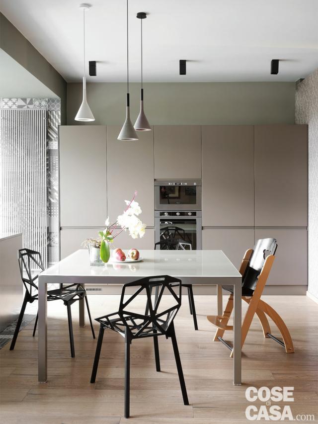 zona pranzo, sedie di design, seduta ergonomica, tavolo con piano in vetro, lampade  a sospensione coniche, faretti
