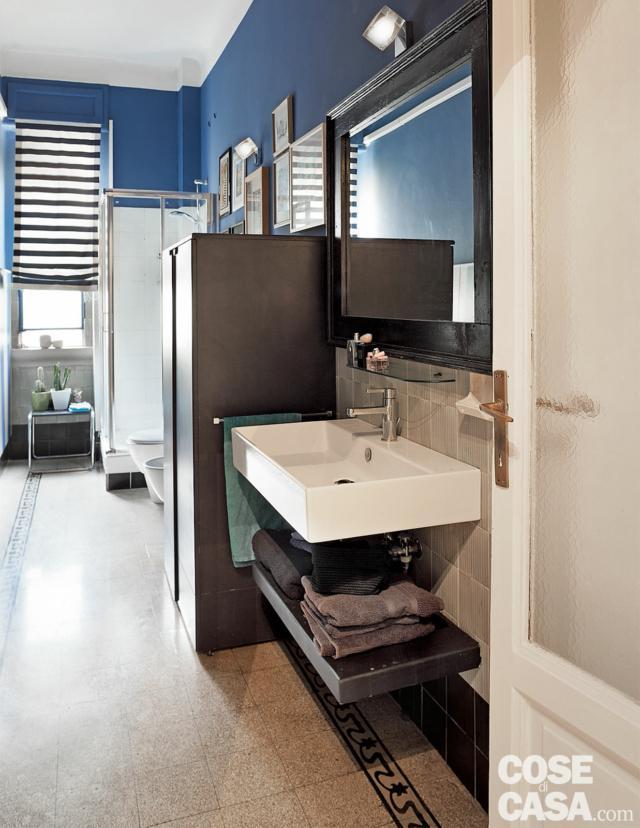 bilocale tradizionale, bagno lungo e stretto, pavimento in cementine, lavabo e ripiano sospesi, pareti blu, armadio, box doccia, finestra