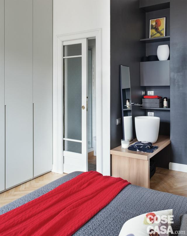camera matrimoniale, porta scorrevole in legno e vetro, angolo con lavamani e nicchia, dettaglio letto, armadio in laccato bianco
