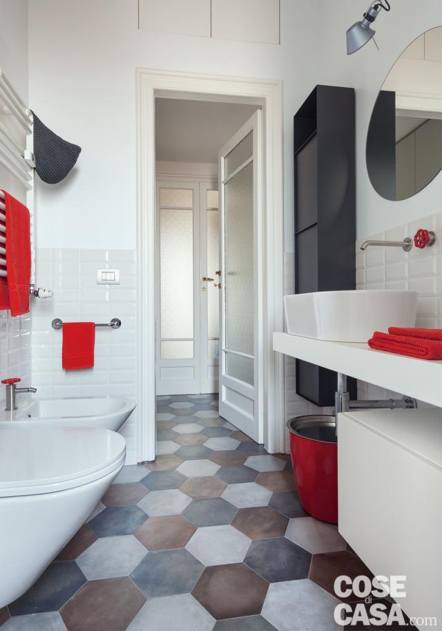 bagno, piastrelle esagonali, porta in legno e vetro, sanitari sospesi, piano con il lavabo da appoggio, specchio, applique, scaldasalviette