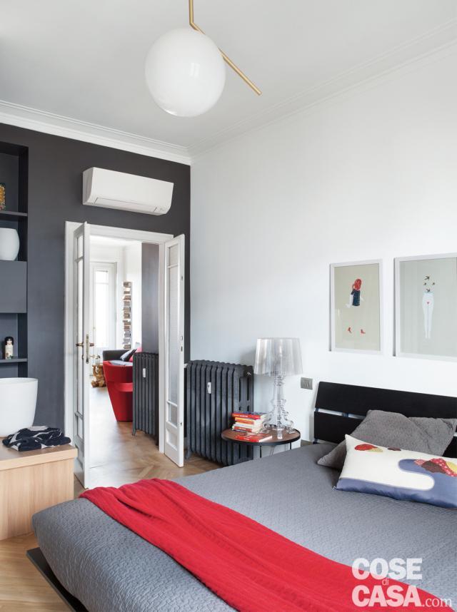 camera matrimoniale, letto con testiera a doghe, plaid rosso, radiatore in ghisa, lampada a sospensione di design, climatizzatore split, parete in finitura grigio scura