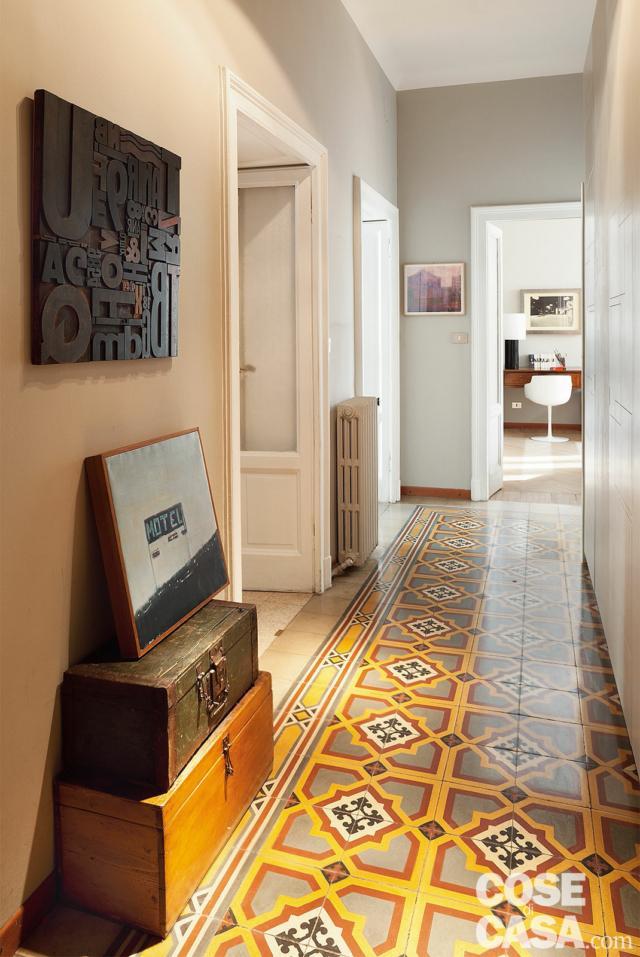 Corridoio, pavimento in cementine, porte in legno laccato bianco e vetro, bauli, radiatore in ghisa