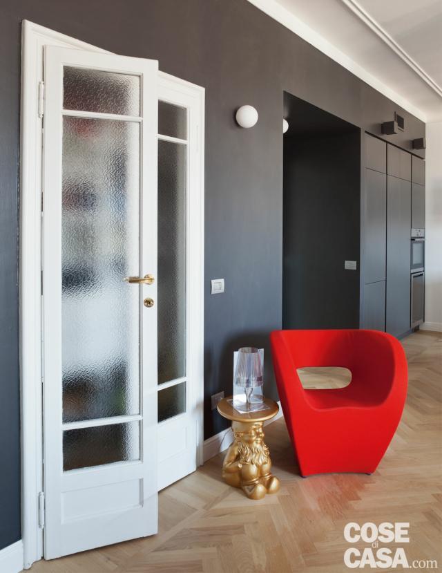 porta in legno laccato a doppio battente, vetro serigrafato, parete in finitura scura, applique sferica, poltroncina rossa e tavolino di design, parquet a spina di pesce