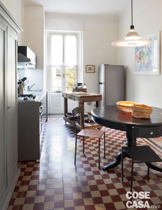 cucina, tavolo da pranzo tondo, lampada a sospensione, sgabello, pavimento in cementine a due colori, composizione in linea, tavolo d a lavoro, finestra, frigorifero freestanding nell'angolo