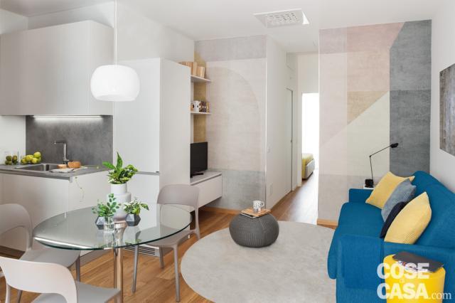 bilocale mini, zona conversazione, divano azzurro, tappeto bianco, tavolo con piano in vetro, sedie, angolo cottura, mobile tv