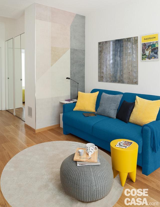 bilocale mini, zona conversazione, divano azzurro, cuscini gialli, pouf, tavolino, tappeto bianco, parete decorata con figure geometriche