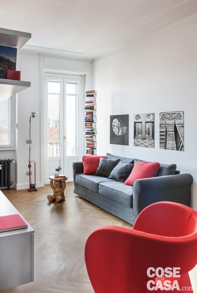 bilocale aperto, soggiorno, divano, poltroncina rossa, portafinestra, colonna portacd, lampada da terra, rivestimento in parquet