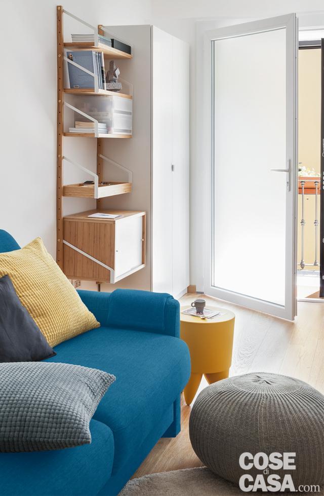 bilocale mini, ingresso, porta vetrata, armadio, libreria in legno, divano azzurro, pouf, tavolino giallo