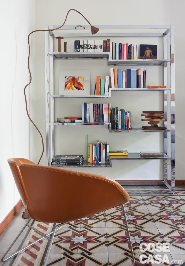 camera, libreria a giorno in metallo, poltroncina rivestita in pelle, lampada snodabile, pavimento in cementine