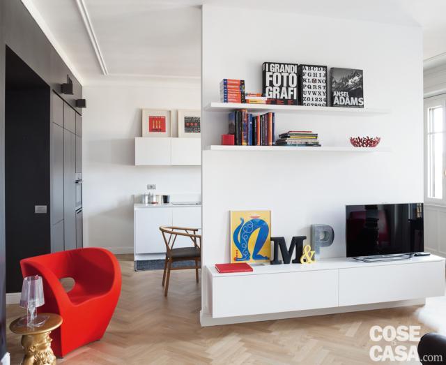 soggiorno, quinta, mobile tv sospeso in laccato bianco, ripiani, poltroncina rossa, parquet a spina di pesce, tavolino e lampada di design