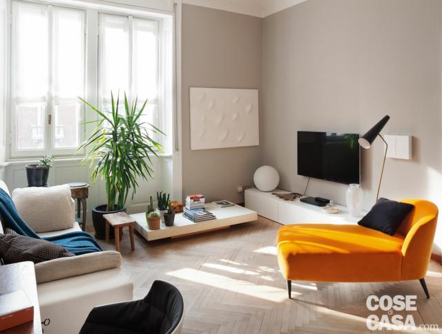 bilocale tradizionale, soggiorno, finestre, zona tv, chaise-longue arancione, divano, coffee table, parete color tortora, pavimento in parquet a spina di pesce