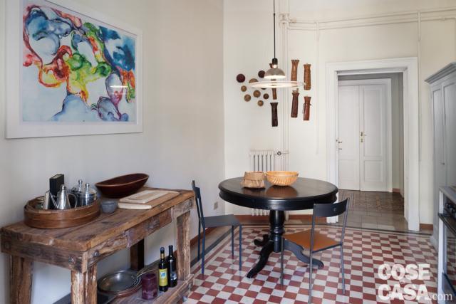 cucina, tavolo da pranzo rotondo in legno, tavolo da lavoro in legno grezzo, lampada a sospensione, pavimento in cementine, radiatore in ghisa, quadro